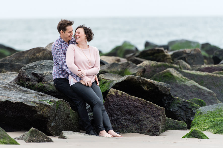 couple sitting on rocks on the beach at coney island