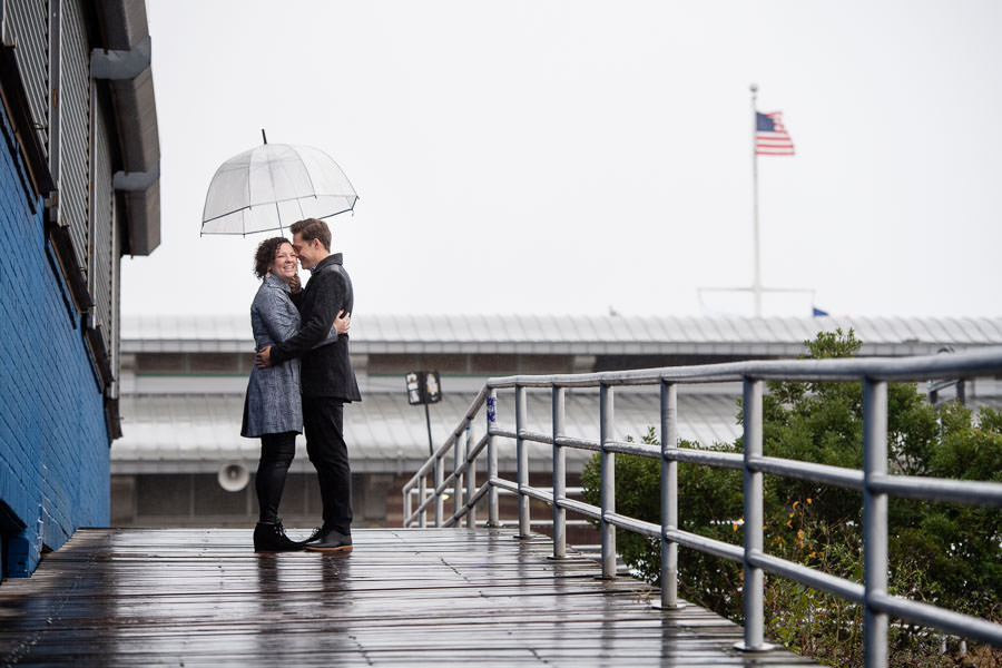 guy and his fiance stand under see through umbrella on the boardwalk in coney island on a rainy day