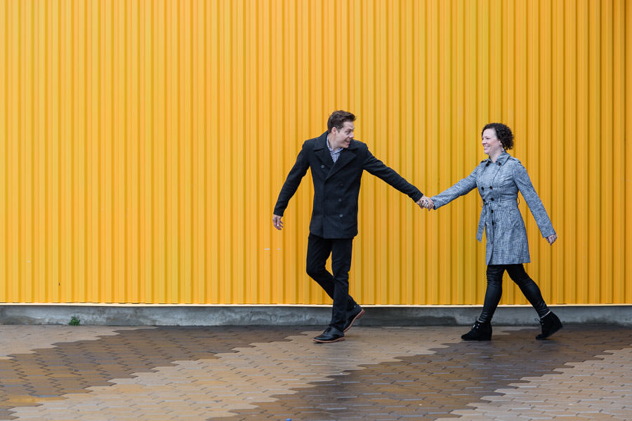 engaged couple running with a yellow wall as a backdrop in coney island brooklyn