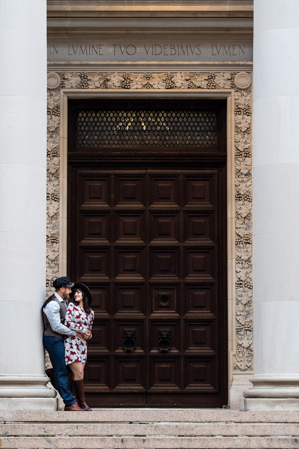 couple poses by big brown wooden door at the columbia university campus in nyc for their engagement session