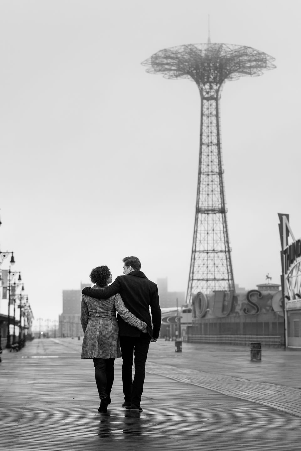 couple walking along coney island boardwalk during engagement session after the rain with parachute jump needle in the background