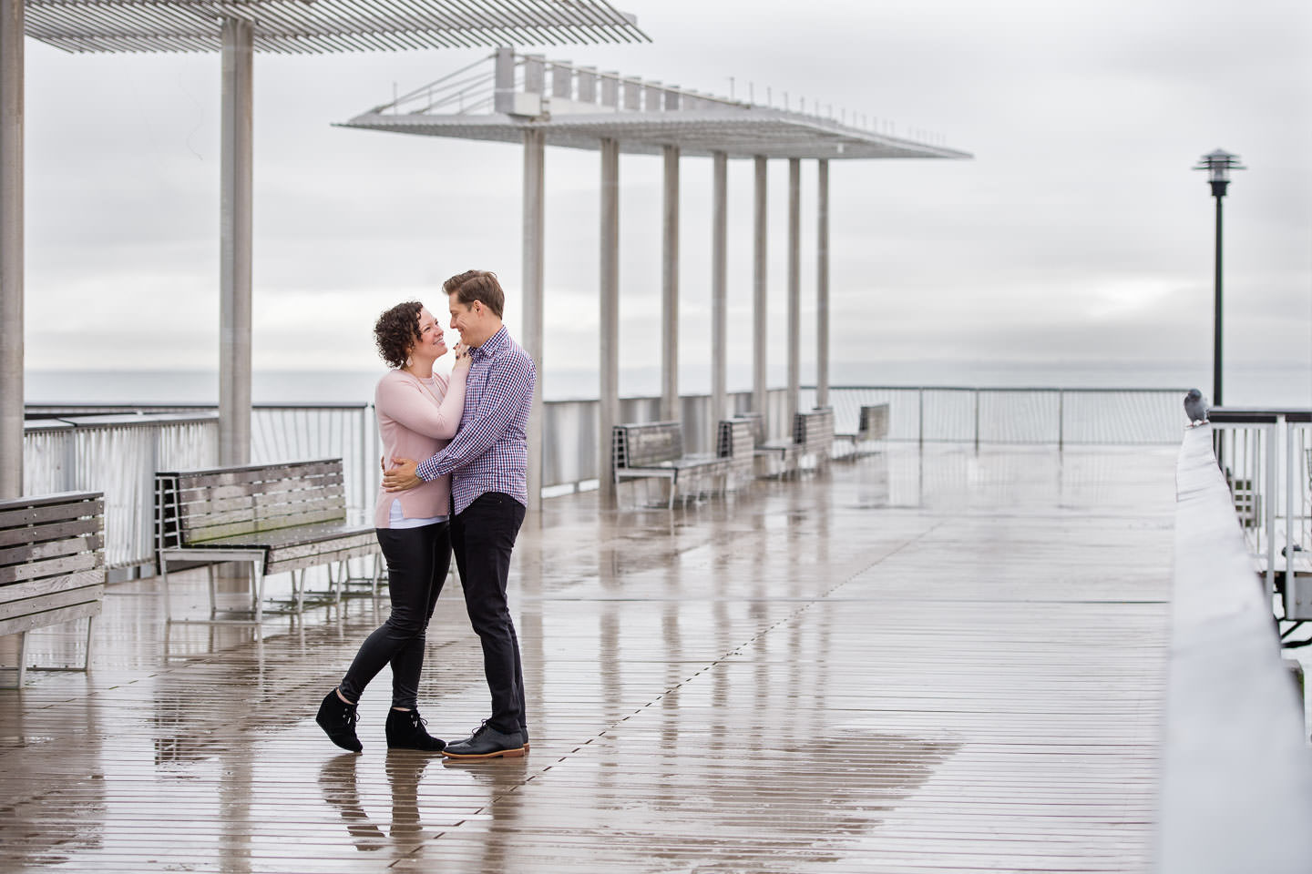 Couple standing and holding each other on the pier with ocean in the background at their Coney Island Engagement Session