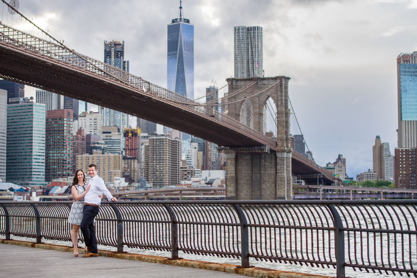 couple holding each other with brooklyn bridge and new york city skyline in the background for their dumbo engagement session