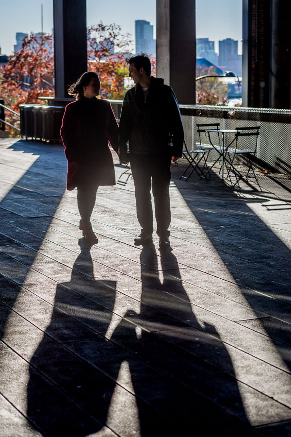 man and woman hold hands and walk with their back to the sun on the highline