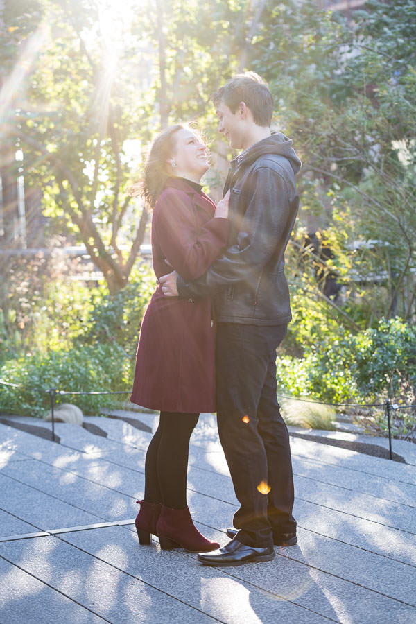 engaged couple stand and hold each other pose for engagement session photo on the highline in nyc