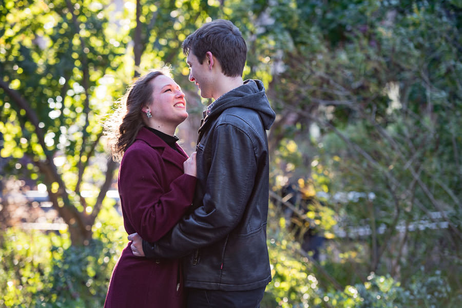 girl smiles with teeth as she looks at her fiance with backlit trees in the background during autumn engagement session in NYC on the highline