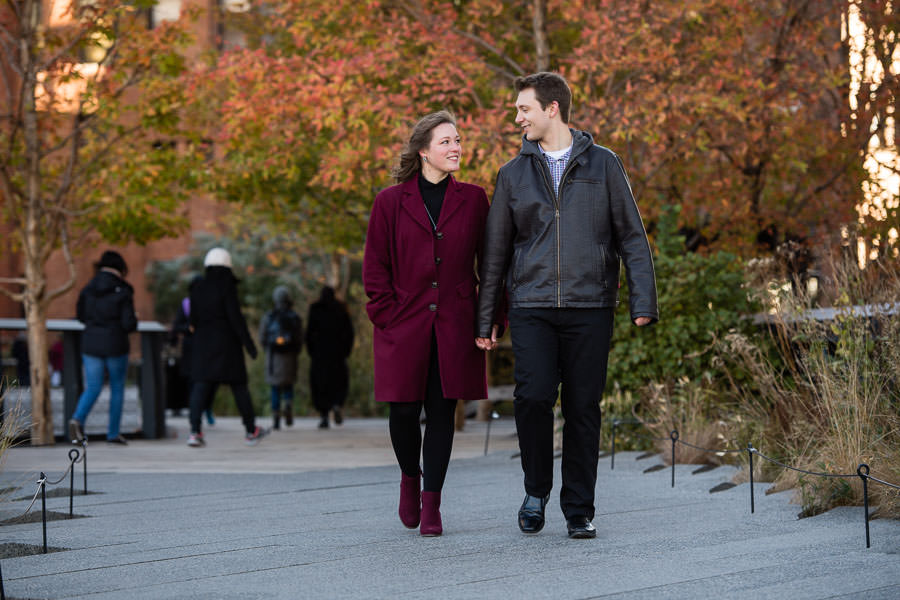 couple walks along the highline in NYC during the Fall with orange trees in the background