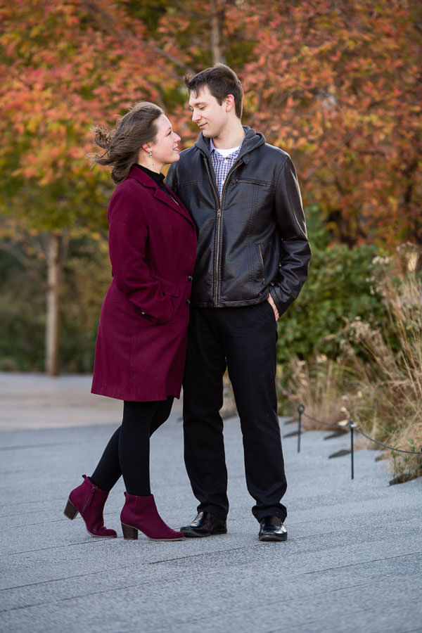 couple standing and looking at each other with fall foliage in the background on the highline park in NYC