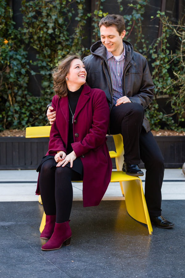engaged couple sit on yellow seat and table during their engagement session in the meatpacking district in NYC