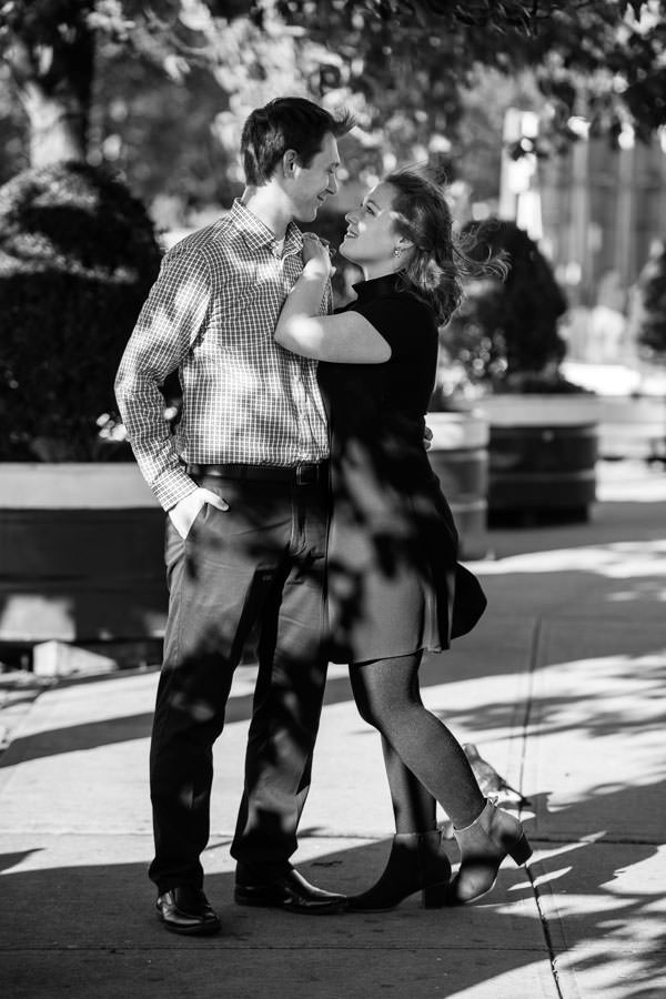 girl holds on to her fiance during their engagement session in meatpacking district in NYC