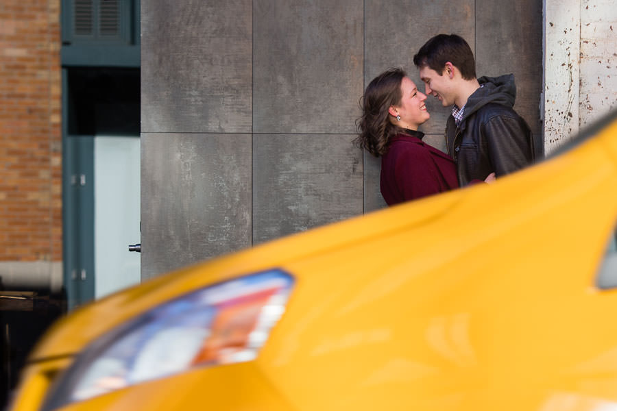 yellow nyc taxi crosses in front of couple as they look at each other during engagement session