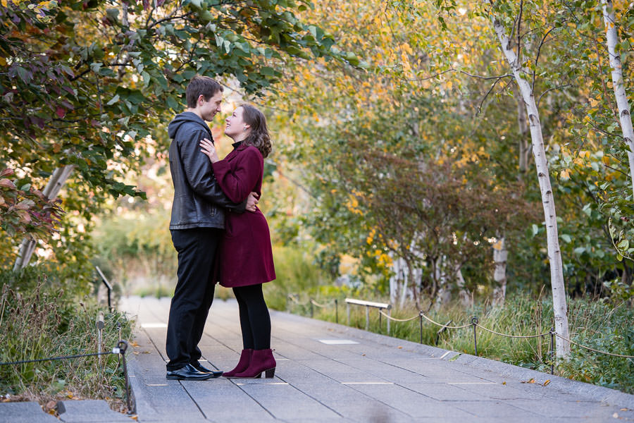 engaged couple hold each other and look at each other during engagement session on the highline in nyc in autumn