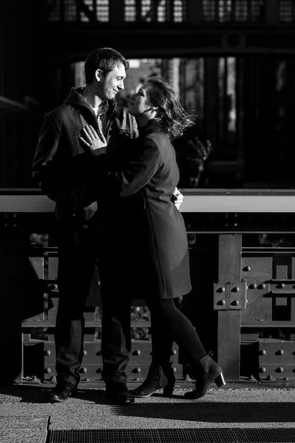 man and woman look at each other in edgy lighting for their engagement session in highline park in nyc
