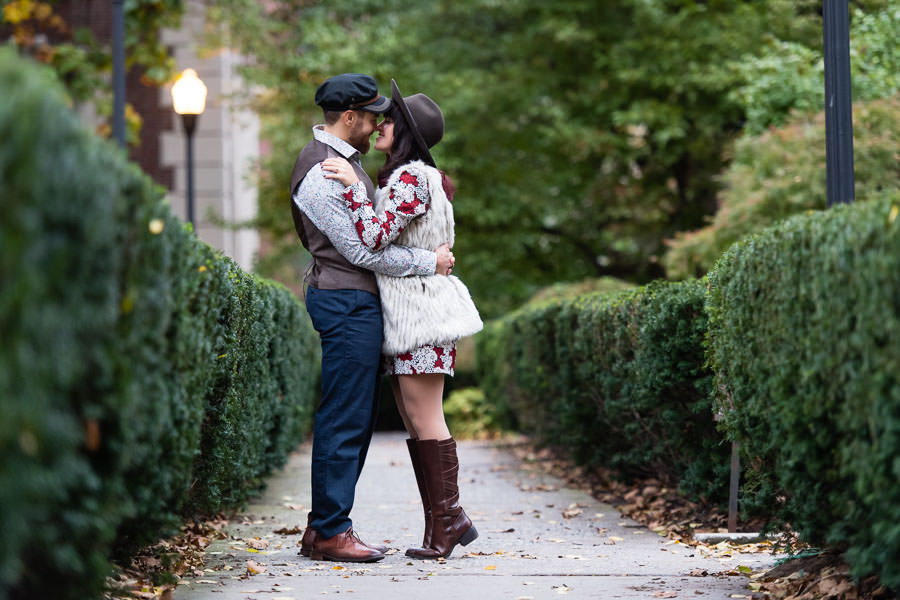 couple stands in path between green bushes at the Columbia University campus for their engagement session