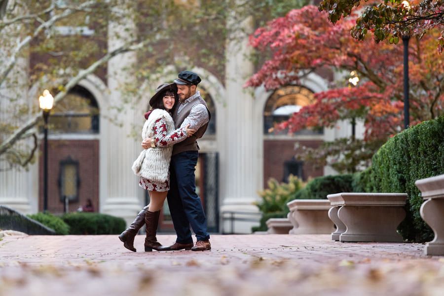 couple stand on path with tree with red leaves in the background on cobblestone path in NYC for their engagement session