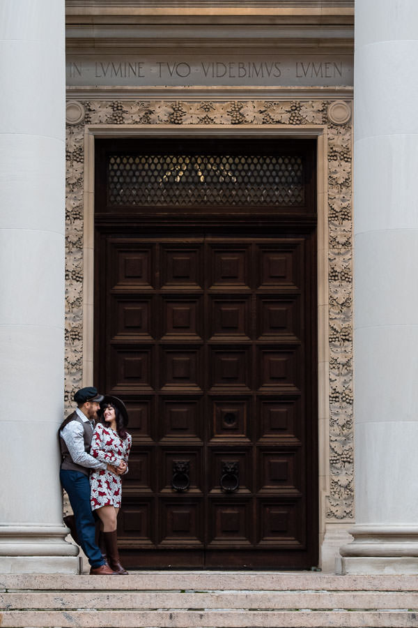 engaged couple stand in front of big brown door for their columbia university engagement session