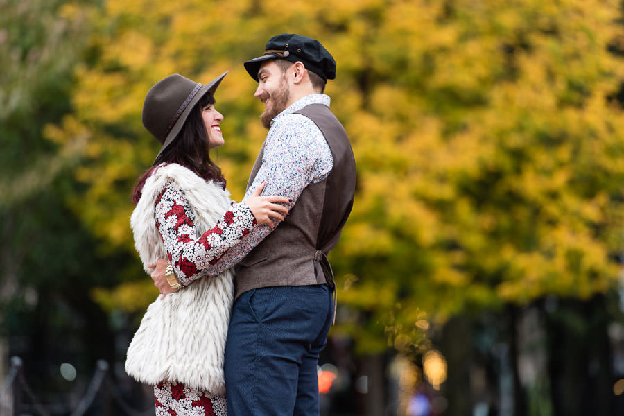 couple wearing hipster clothing and hats smile at each other in front of tree with yellow leaves during their engagement session