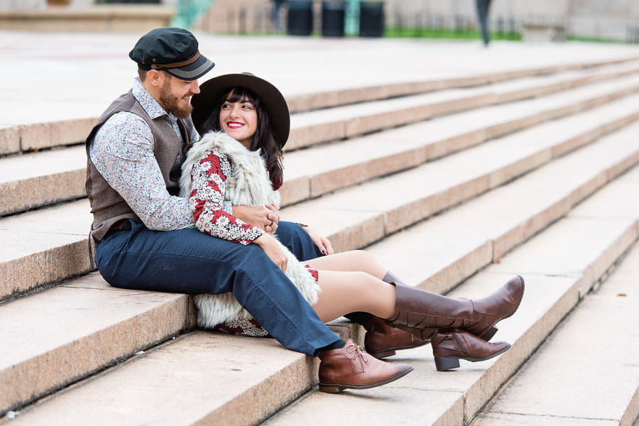 couple sits on steps at columbia university in NYC during their engagement session girl is wearing hat and boots and fur vest and guy is wearing hat with vest and brown shoes