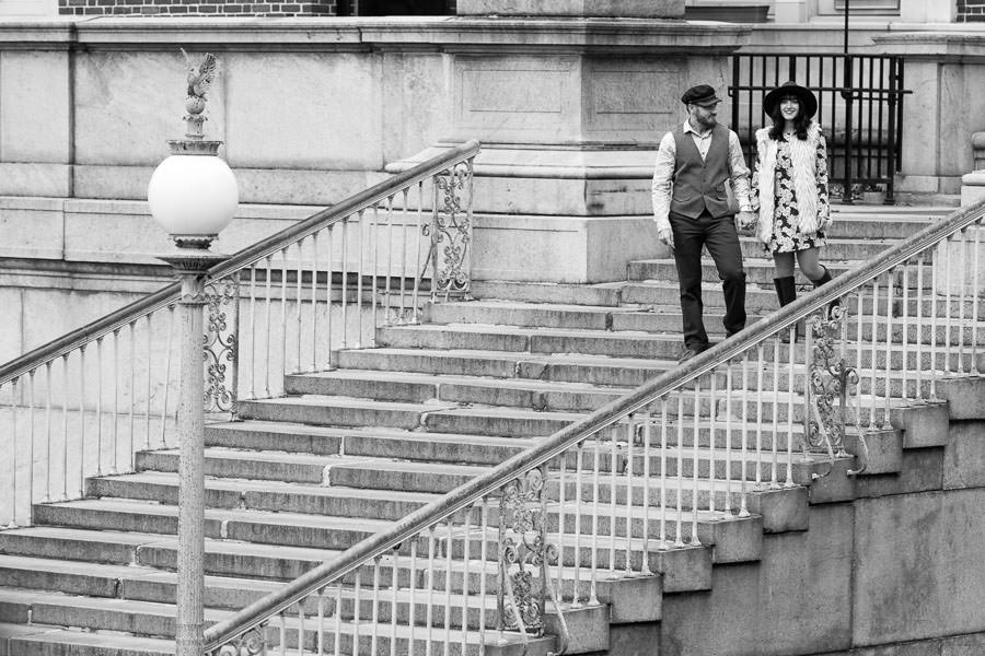couple holds hands and walks down steps during the engagement session at Columbia University in NYC