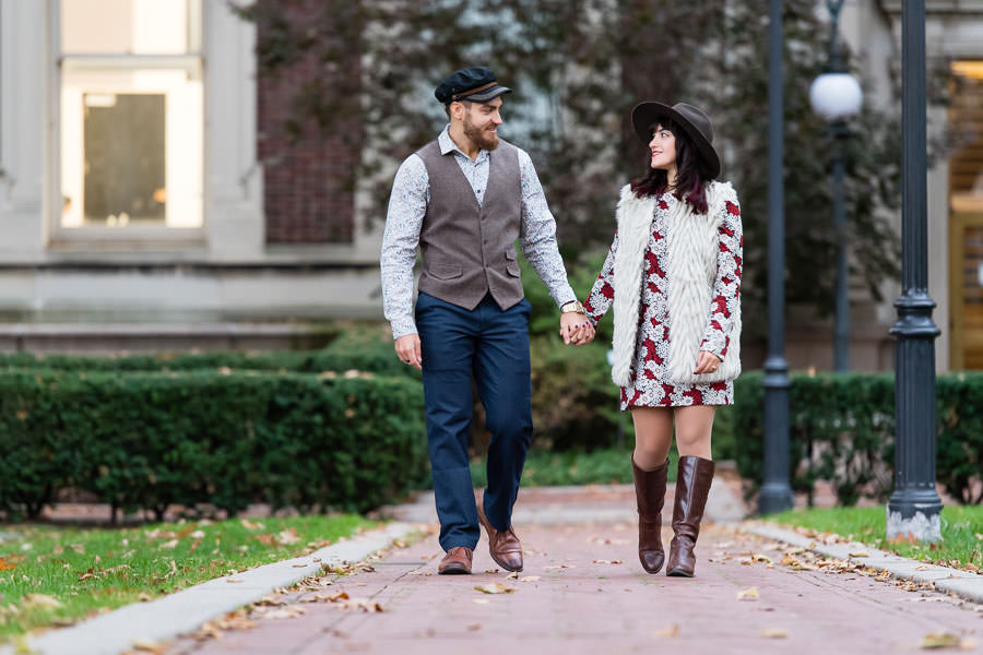 man and woman hold hands and walk down path together at the Columbia University campus in NYC