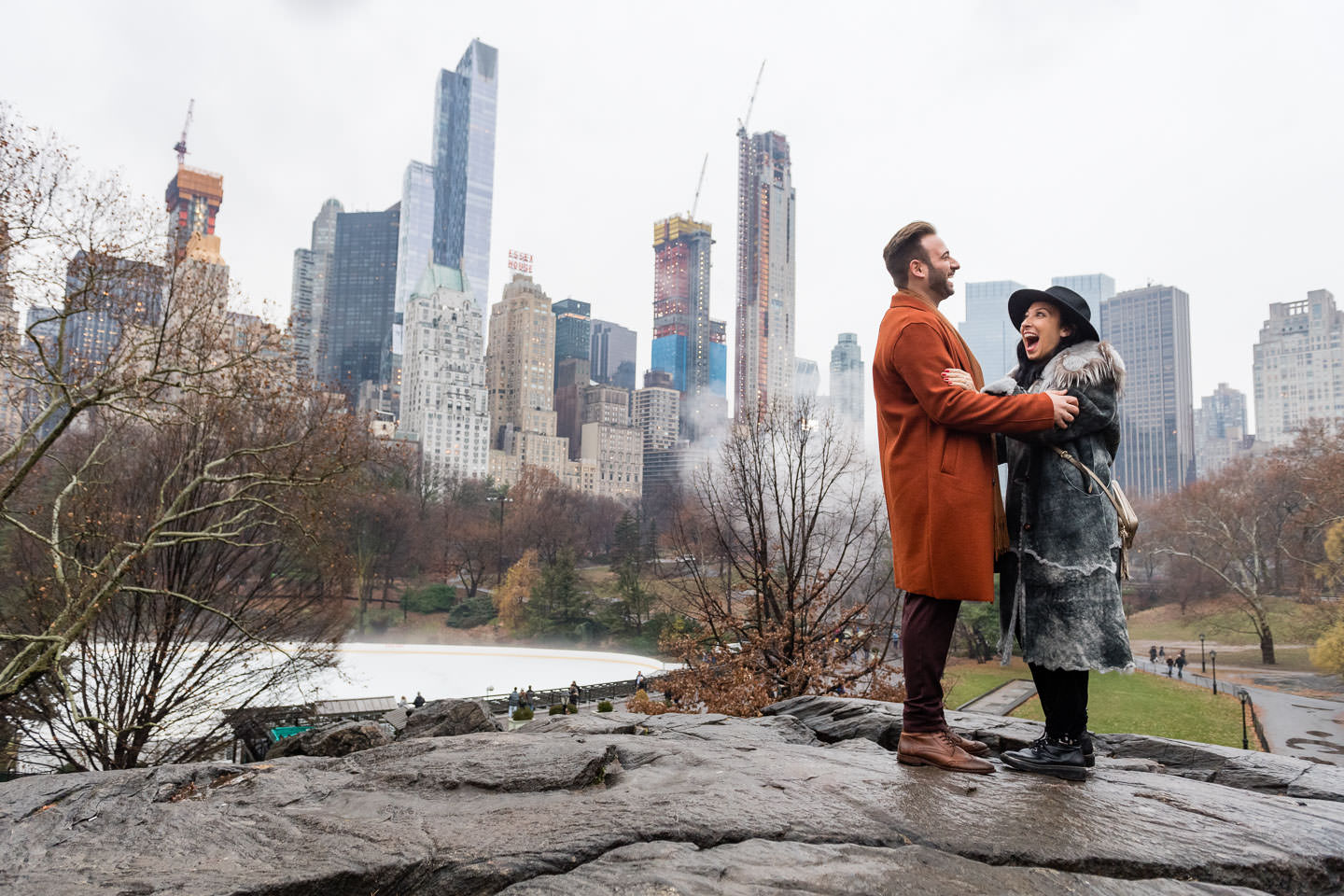 engagement session in central park by gapstow bridge in front of wollman rink