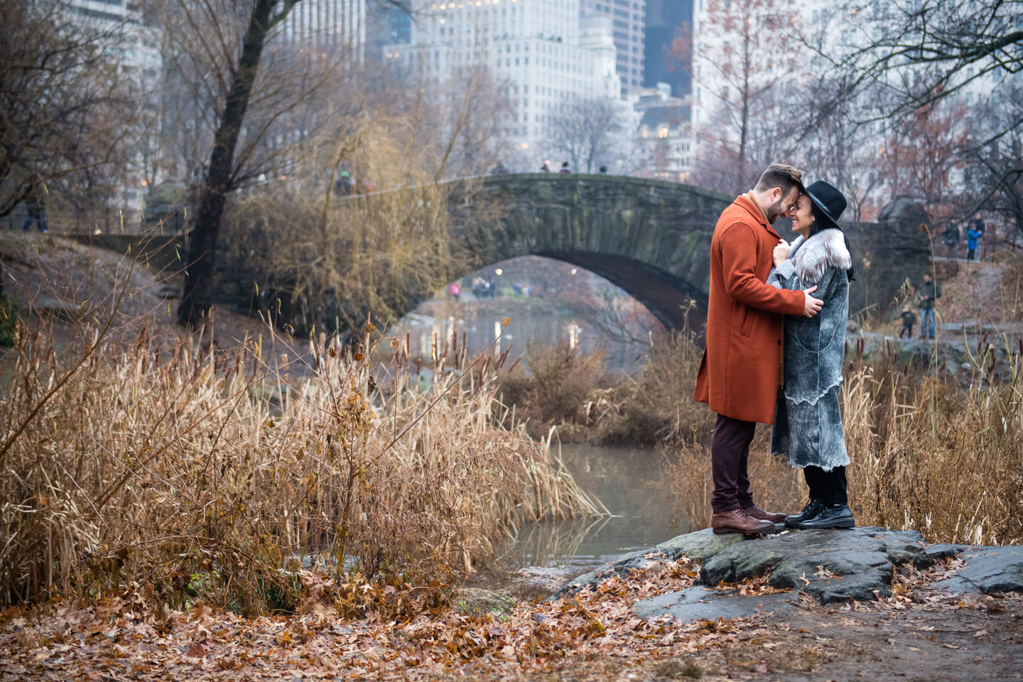 couple poses for engagement session by Gapstow bridge in Central Park