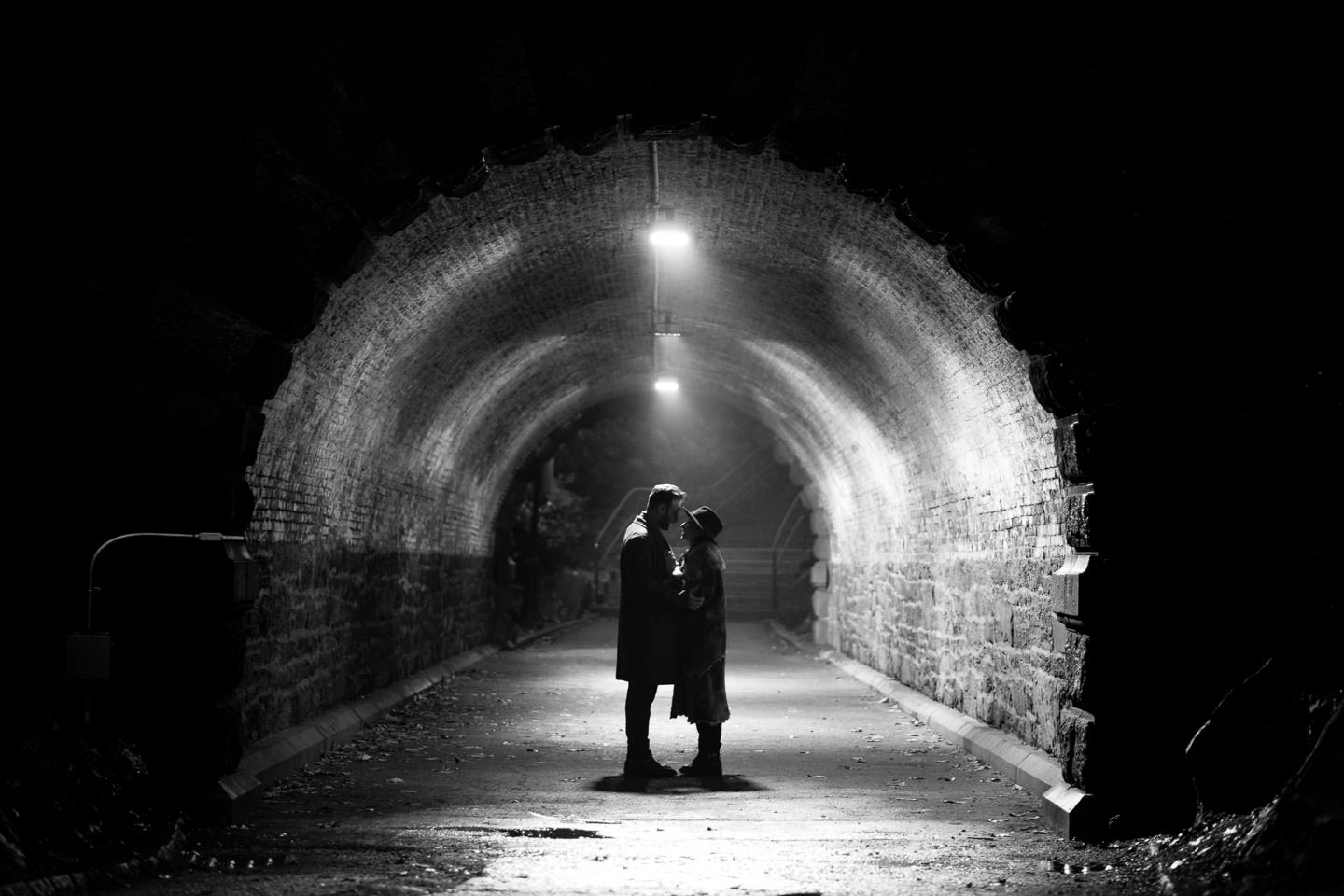 couple standing in the middle of a tunnel in central park engageement session