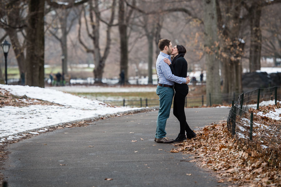 engaged couple hold each other and kiss in central park in the winter with snow on the ground