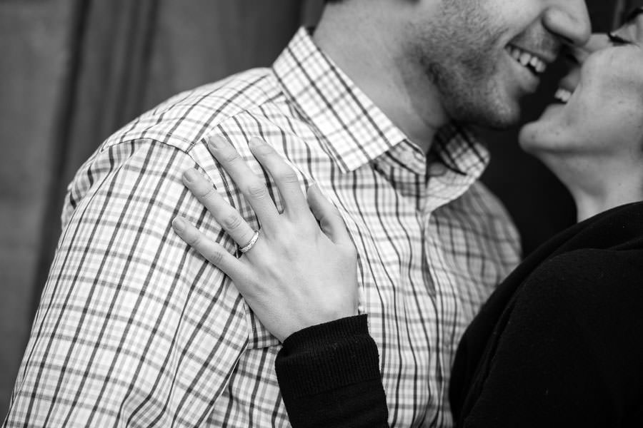 close up of engagement ring resting on guys shoulder while couple kissing