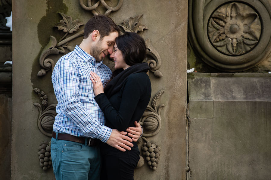 couple holding each other during engagement session in central park near bethesda terrace