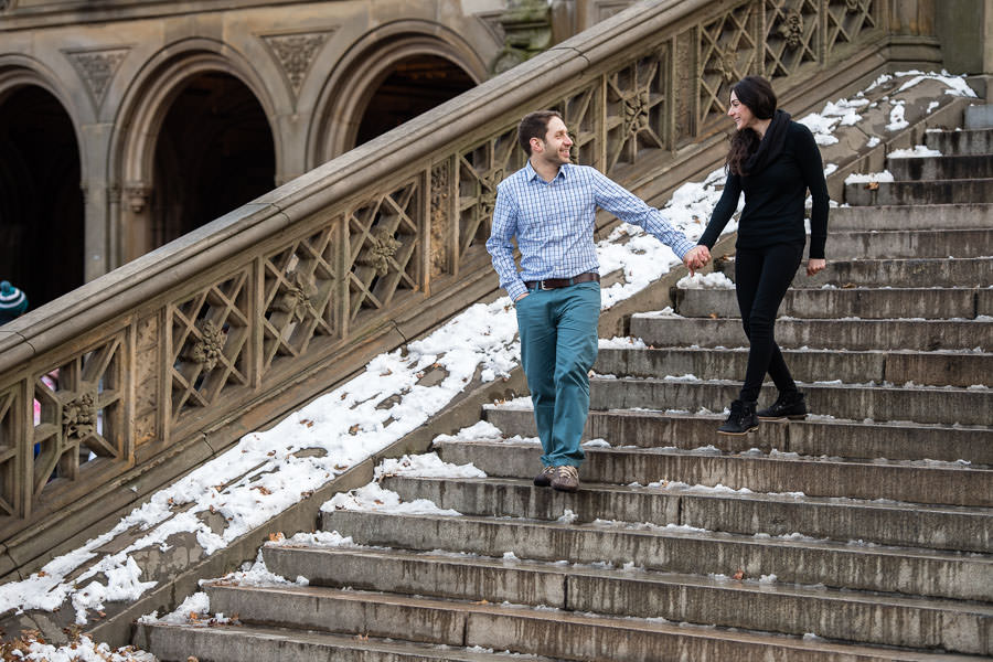 Bianca and Joe holding hands as they walk down the snowy stairs from Bethesda Terrace in Central Park