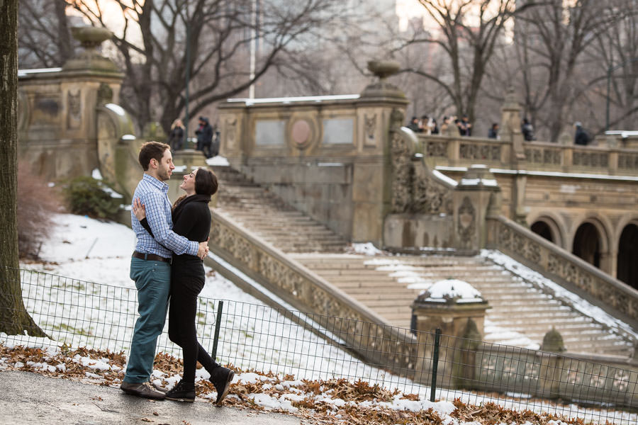 Bianca and Joe look at each other as they hold each other tight to stay warm during their winter central park engagement session