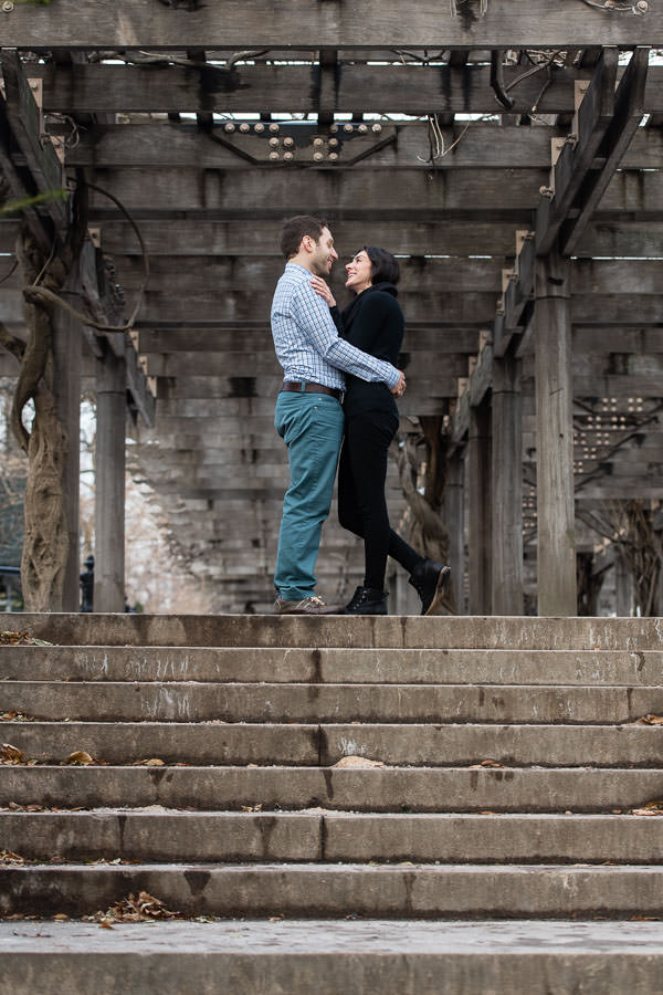 couple standing together at the top of the steps with wooden structure in central park