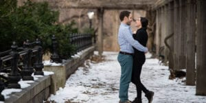 joe and bianca look at each other smiling while standing in central park in the winter with snow on the ground and pine trees to the left under a wooden structure
