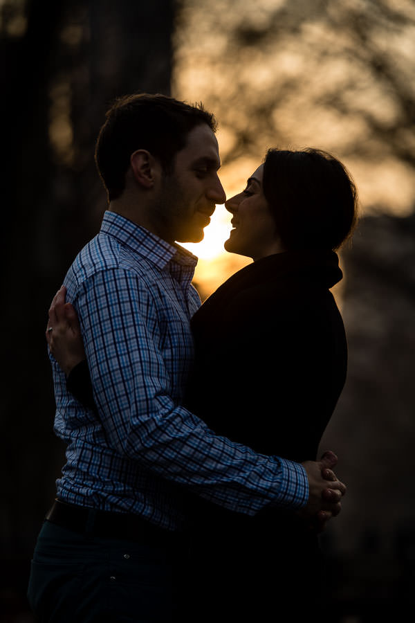 engagement session in central park ends with sunset and couple putting their faces together to form a silhouette