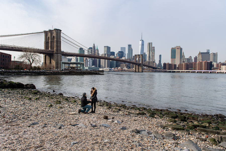 guy proposes to his girlfriend at pebble beach in dumbo brooklyn at the east river with brooklyn bridge and downtown manhattan skyline in the background