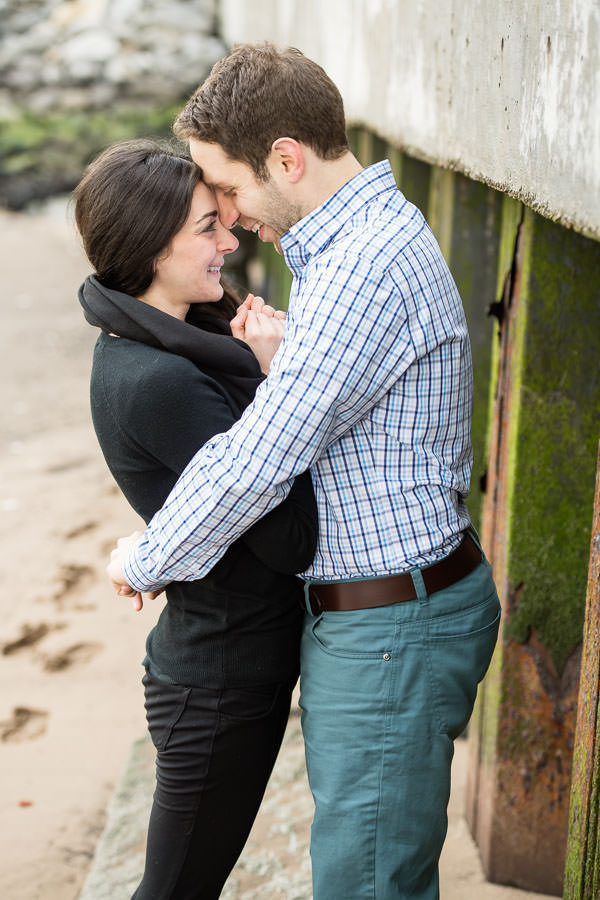 couple holds each other close and smiles at each other while standing on the beach by the east river shore in nyc