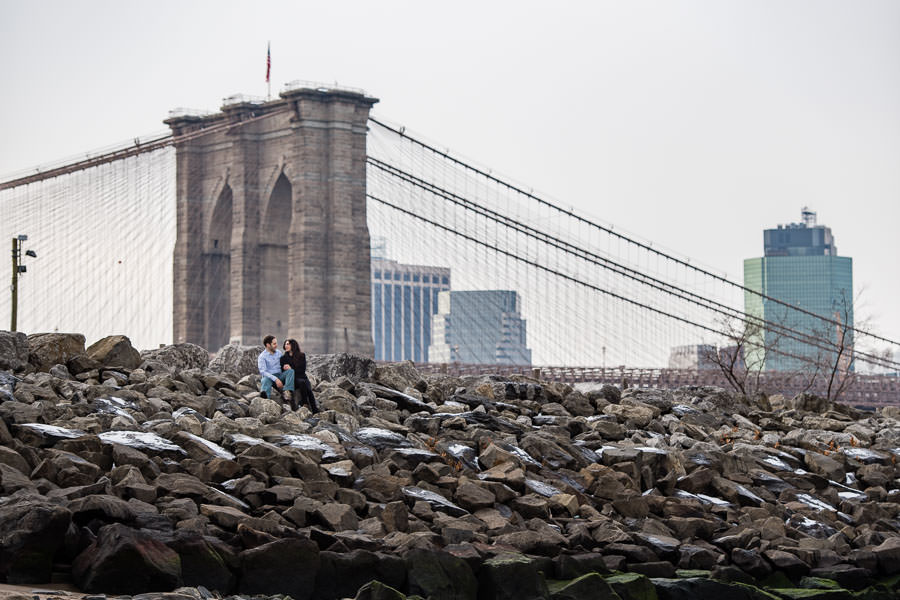 couple sits on boulders surrounding the shore of the east river with the brooklyn bridge in the background