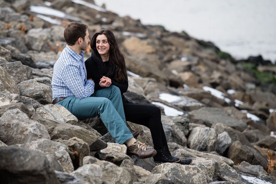 close up of couple sitting together on rocks in dumbo brooklyn holding each other