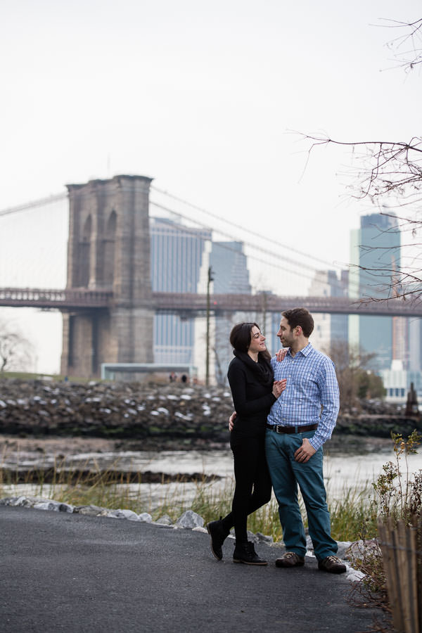 couple stands in front of brooklyn bridge and the east river