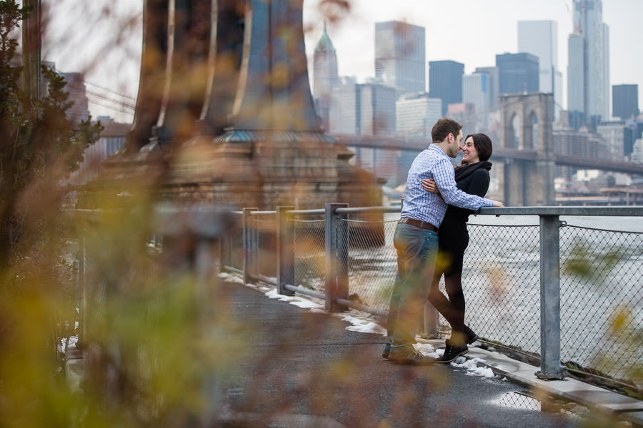 couple hold each other and rub noses together while leaning against fence in dumbo with brooklyn bridge in the background