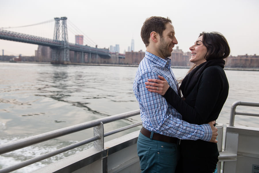 engaged couple hold each other on the east river ferry in nyc with williamsburg bridge in the background