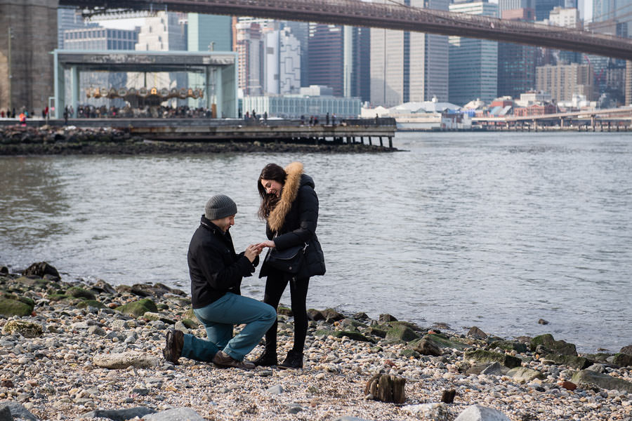 Marriage proposal in Dumbo Brooklyn New York City on Pebble beach by the east river with the brooklyn bridge in the background