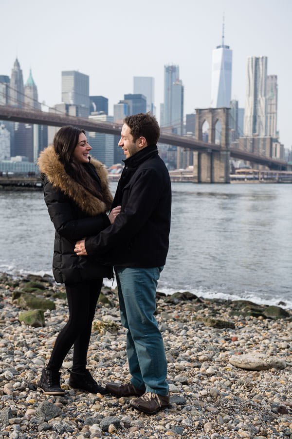 engagement session with couple looking at each other smiling with brooklyn bridge and the freedom tower in the background