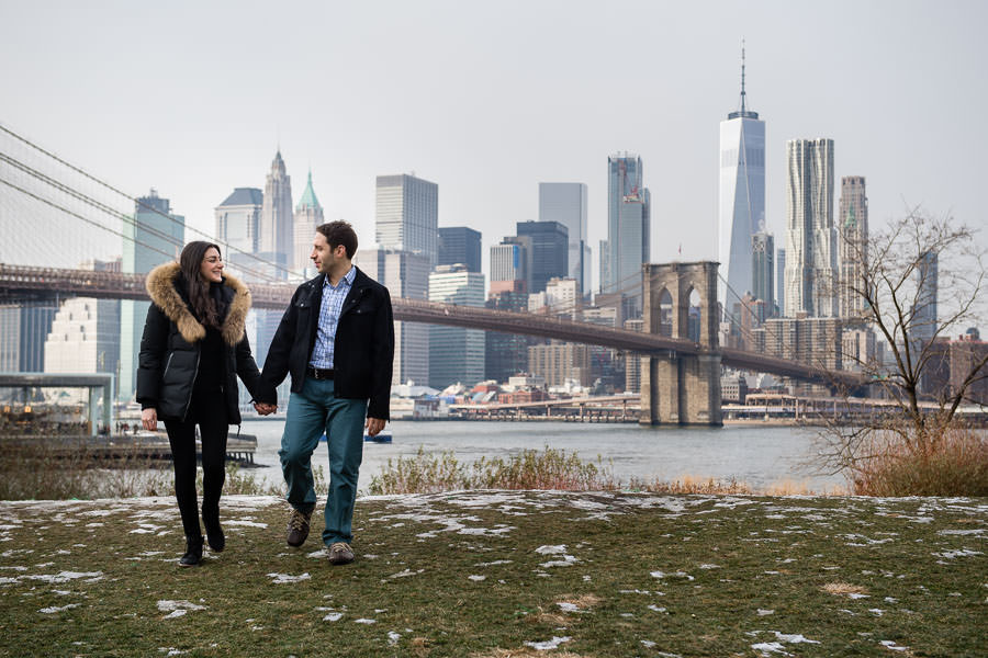 couple holding hands and walking on the grass covered in snow with nyc skyline in the background with brooklyn bridge and downtown manhattan