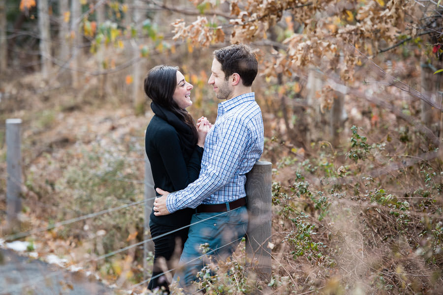 couple hold each other and laugh with winter foliage surrounding them