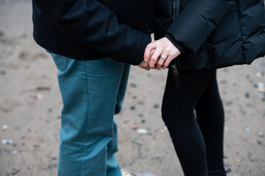 close up shot of couple holding hands and engagement ring visible