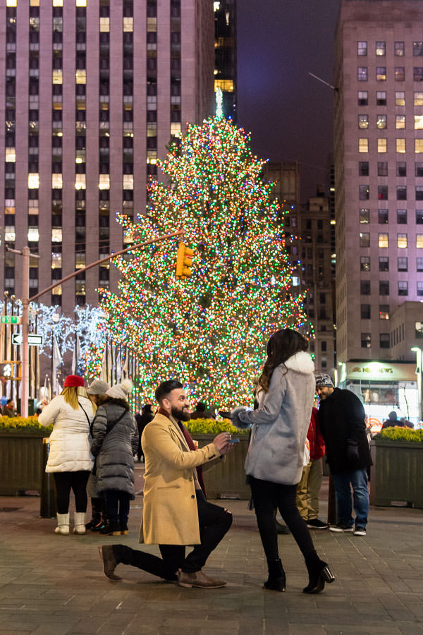 Jasvinder drops to one knee to propose to his girlfriend in front of the tree at Rockefeller center. Night time proposal at Rockefeller center