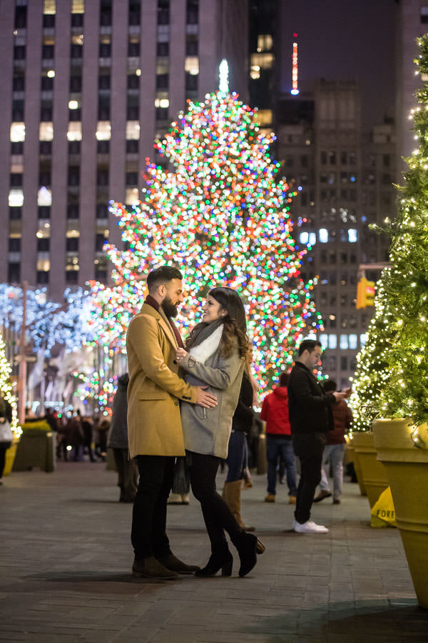 Jasvinder and Nikky hold each other after their proposal at Rockefeller Center at night