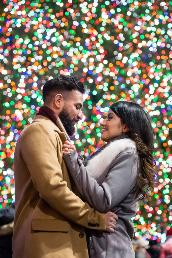 Jasvinder and Nikky hold each other close with the rockefeller center tree in the background big and out of focue